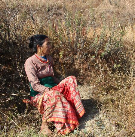 a Nepalese woman sitting next to an indigenous tree seedling planted within the EbA South project. This woman ensured all seedlings on her land were weeded and fertilized regularly.